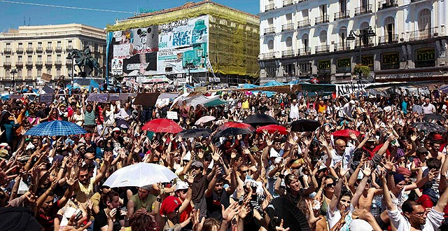 Los 'indignados' levantan sus manos para aprobar continuar la protesta. | Reuters