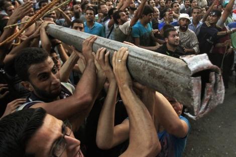 Un grupo de manifestantes trata de hacer caer el muro. | Reuters