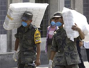 Dos soldados mexicanos llevan paquetes con máscaras para la población en la capital.   Reuters