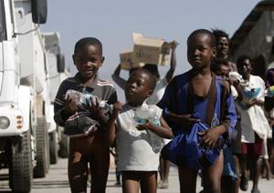 Un grupo de niños carga botellas de agua y paquetes de alimento en el reparto de suministros. (Foto: Orlando Barría)