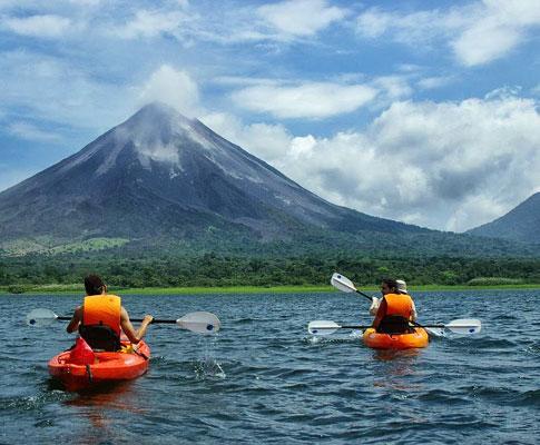 Practicando rafting con el volcán Arenal al fondo.