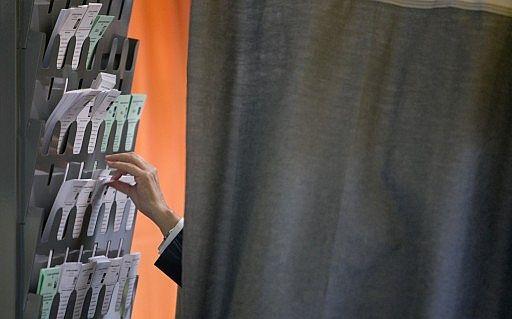 Un ciudadano escoge papeleta antes de ejercer su voto en la urna