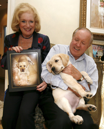 Nina y Edgar Otto posan con su labrador clonado, Sir Lancelot Encore, y una foto de su 'versión original' fallecida. | Efe