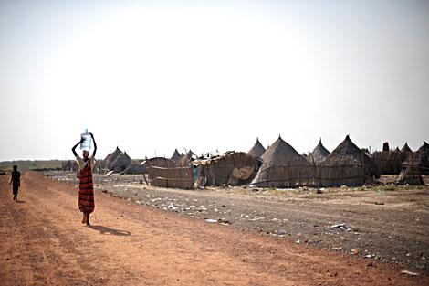 Una mujer sudanesa lleva un bidón de agua en la cabeza. | AFP