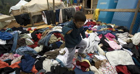 Un niño salta sobre una montaña de ropa donada tras el seísmo. | Efe