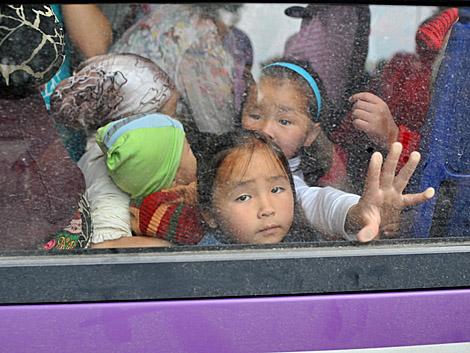 Varios niños apinñados en un autobús para viajar de Osh a Bishkek. | Afp