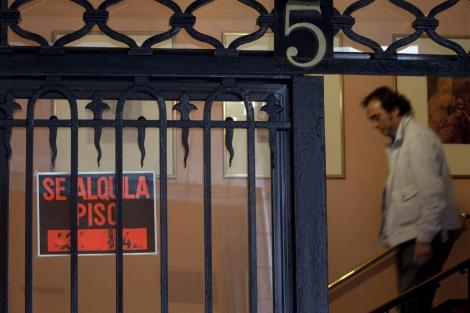 Imagen de una fachada con un cartel que anuncia el alquiler de un  piso