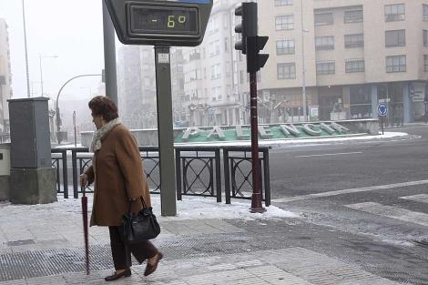 Una mujer pasa delante de un termómetro en Palencia que marca 6 grados bajo cero. | Efe