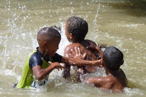 Unos niños colombianos juegan en el agua. | Plan