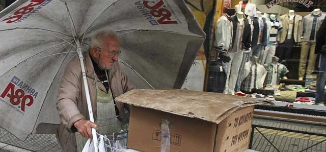 Un vendedor callejero empuja su carrito bajo la lluvia en Atenas este viernes. | Efe