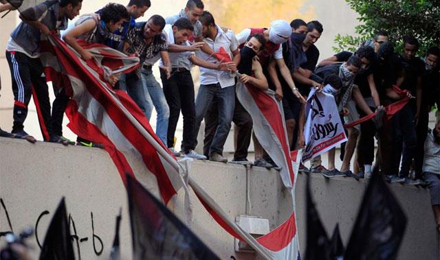 Manifestantes egipcios sobre el muro de la embajada norteamericana en El Cairo. | Reuters