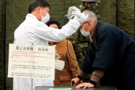 Un médico mide la radiación de un residente de Otama, cerca de Fukushima.   Efe