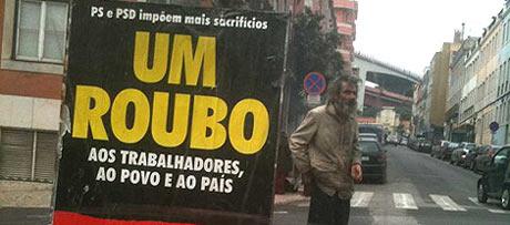 Una persona sin hogar, en una calle de Lisboa, junto a un cartel de la huelga.| A. F.