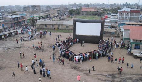 En el poblado de Kiberia se reúnen en torno a la pantalla. | Hot Sun Foundation