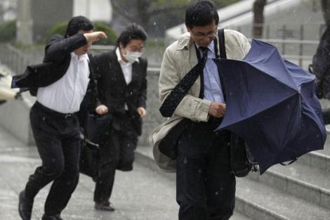 Varios trabajadores vuelven a casa a causa de la tormenta, ayer, en Tokio. | Reuters