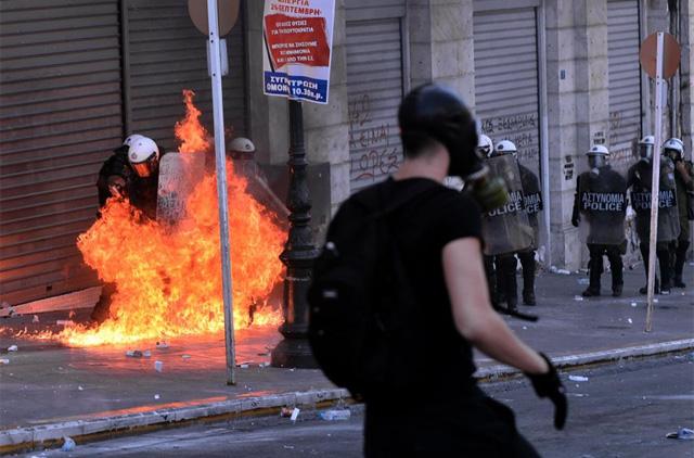 Policías junto a las llamas de un cóctel incendiario. | Afp