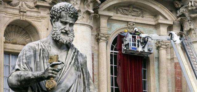 Bomberos decoran con terciopelo rojo el balcón central de la Basílica de San Pedro.| Efe