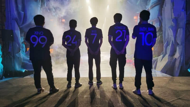 The roster for PSG.LGD stand facing the AniMajor stage ahead, their tagnames are visible on the backs of their jerseys