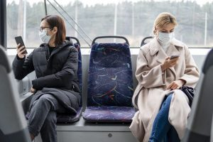 two women on a bus wearing face masks looking at their phones