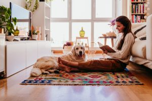 Woman enjoying a cup of coffee during healthy breakfast at home. Writing on notebook. Adorable golden retriever dog besides.