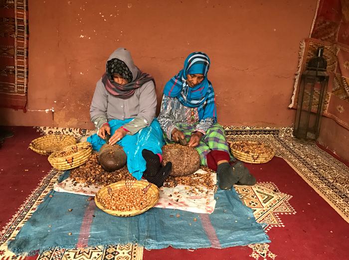women cracking argan nuts in morocco