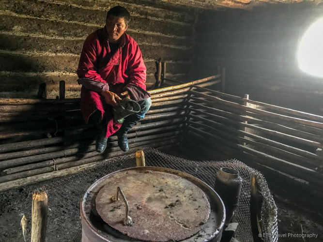 Mongolian cowboy in warming room at winter camp