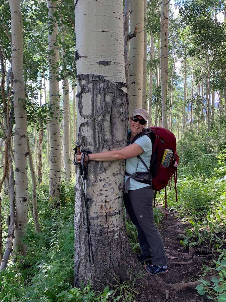 Diana hugging big aspen tree