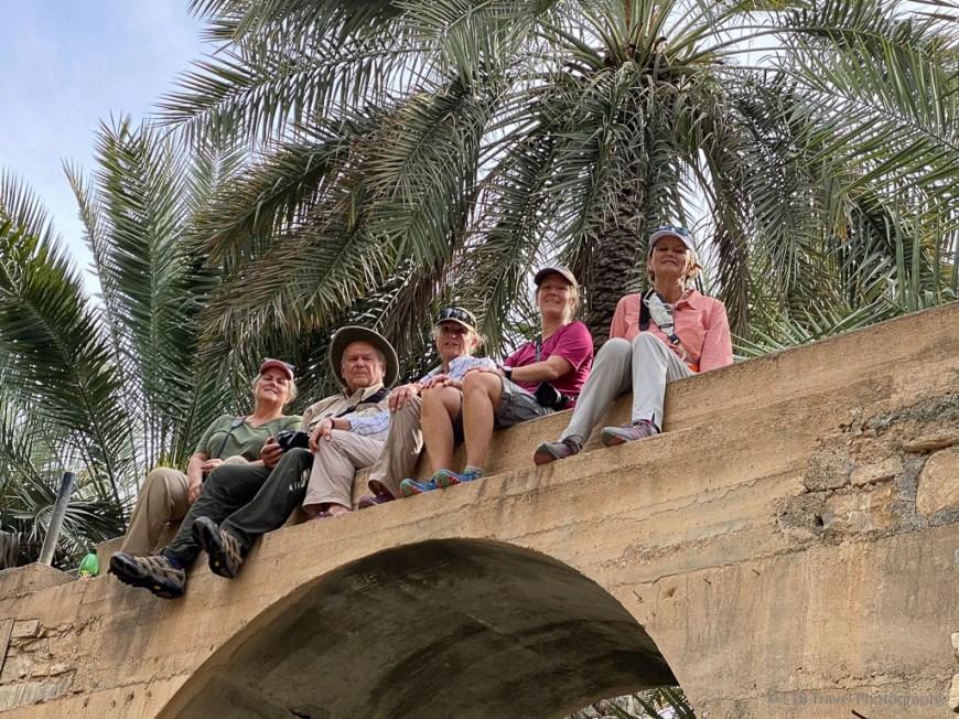 sitting on falaj at birkat al mawz