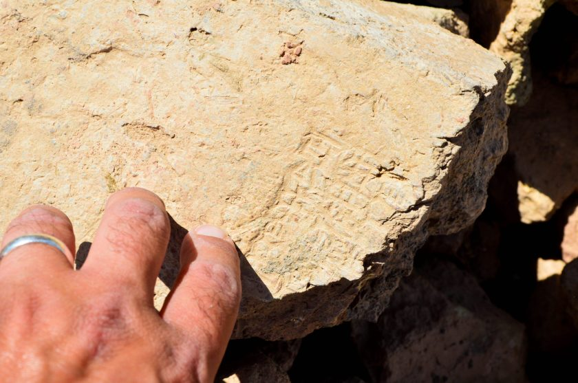 A fragment of a mud-brick which was stamped with cuneiform inscriptions. My left fingers touch and feel the brick! Awesome!
