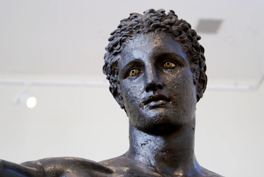 Known as the Antikythera Ethebe, the statue is one of the very few surviving ancient Greek bronzes and is a masterpiece of Greek Classical sculpture (c. 340 BCE) The statue may represent either Hercules holding the apples of the Hesperides or Perseus holding the head of the Gorgon Medusa. (National Archaeological Museum, Athens). Photo by Dimitris Agelakis, CC-BY-NC-SA.