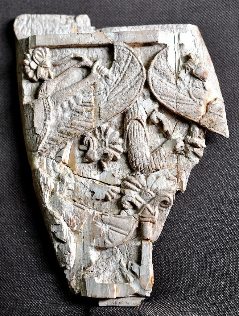 A fragment of a carved ivory plaque. On the left, the arm of a person holds a branch of lotus. Part of his wing appears. On the right, part of a wing of another person can be seen. Neo-Assyrian period, 9th-7th centuries BCE. From Nimrud, Mesopotamia, Iraq. (The Sulaimaniya Museum, Iraq).