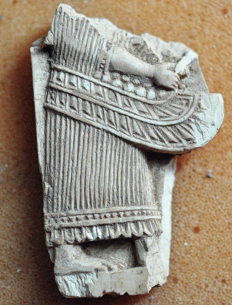 The lower half the body of person with his wing appears in this broken ivory plaque. Neo-Assyrian period, 9th-7th centuries BCE. From Nimrud, Mesopotamia, Iraq. (The Sulaimaniya Museum, Iraq).