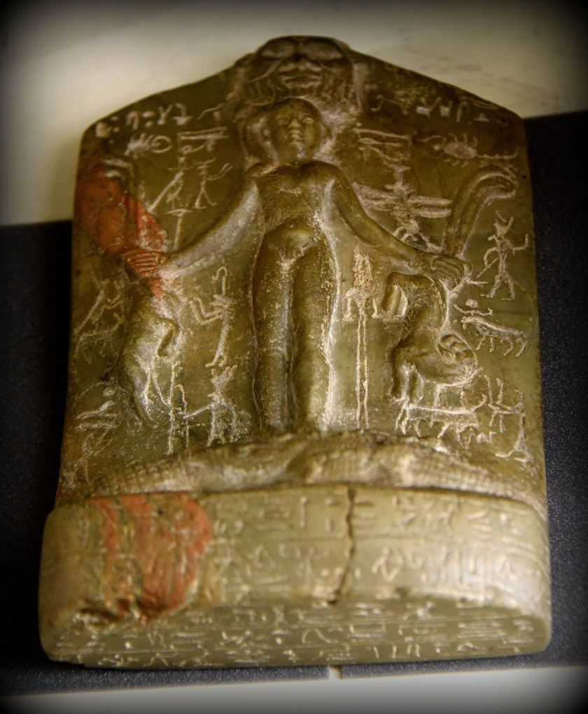 "This is a protective amulet called ""cippus or Horus stela"". It depicts the god Horus as a naked child, standing on 2 crocodiles with oryx and serpents in each hand. God Bes can be seen at the upper part. The cippus is inscribed in hieroglyphs on all faces with words to be spoken in defence of health (mainly against snake and scorpion bites). From Egypt. Ptolemaic Period, 305-30 BCE. With thanks to the Petrie Museum of Egyptian Archaeology. Photo © Osama S. M. Amin."