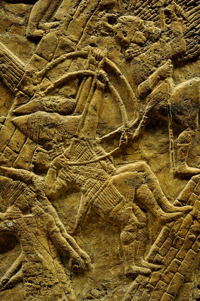 Assyrian slingers and archers are ascending up, on the artificial ramp, to the city walls. They are being led and protected by a spearman who holds a large rounded shield.