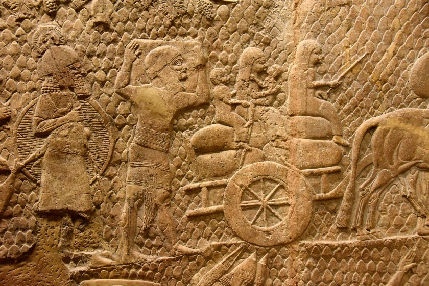 An Assyrian soldier watches a deported family form Lachish. A man holds a large box on his shoulders. A young woman guides a 2-wheeled cart pulled by a bullock while another women holds a boy and a girl. The family tried to bring with them as much as they could of their household belonginngs. From Nineveh (modern-day Mosul Governorate, Iraq), Room XXXVI of the South-West Palace, panels 8-9. The British Museum, London. Photo © Osama S. M. Amin.