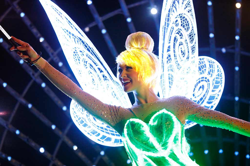 Tinkerbell Waves from atop a nighttime parade float