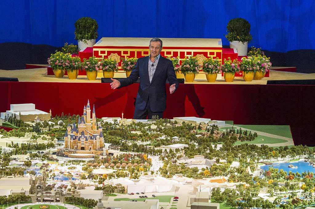 Disney CEO Bob Iger unveils Disneyland Shanghai Plans in front of model.