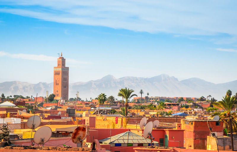 The rooftops of Marrakech with the tall minaret of the mosque and Atlas Mountains in the distance on a sunny day