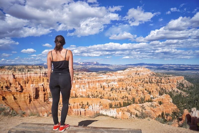 allison looking over the edge of bryce canyon and its orange hoodoos