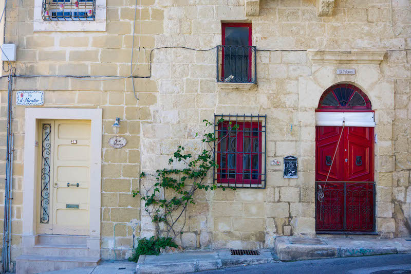 A red door and a red window against sandstone bricks on a historic building in Birgu