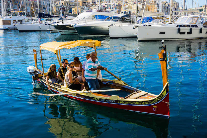 Man steering a traditional colorful boat in Malta
