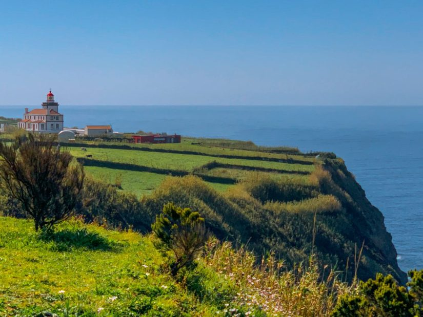 fields with a lighthouse on it overlooking a cliff and the atlantic ocean in the azores