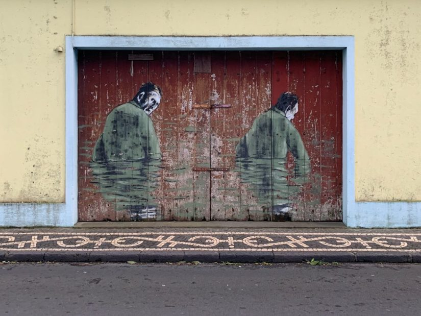 street art of two men's portraits on a garage door. yellow and red.