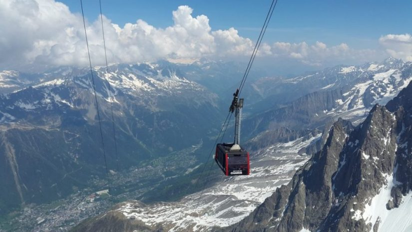 red cable car going up a steep snowy mountain to chamonix mt blanc