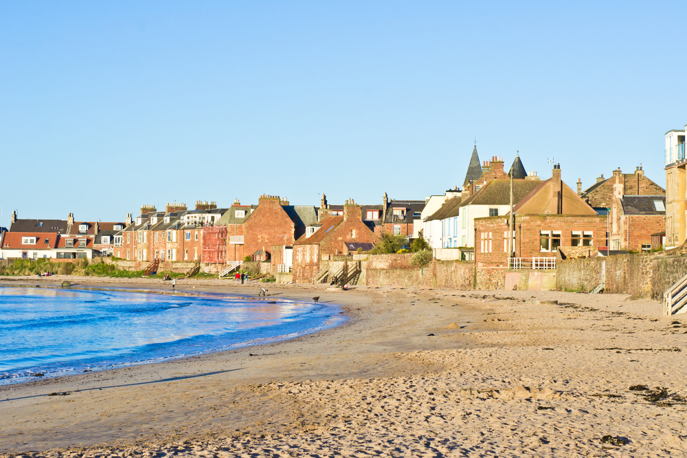Sandy beach on sunny day with houses on shore
