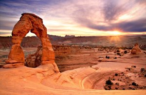 Delicate Arch thin stone arch shown at sunset with red rock background