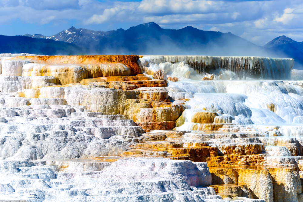 White and rust-colored calcium deposits form a travertine staircase of a hot spring at Mammoth Hot Springs, a must on your 2 days in Yellowstone.