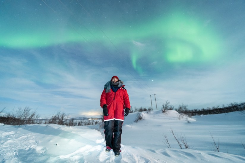 Allison in a large red parka with a swirl of the northern lights appearing in green colors in the night sky