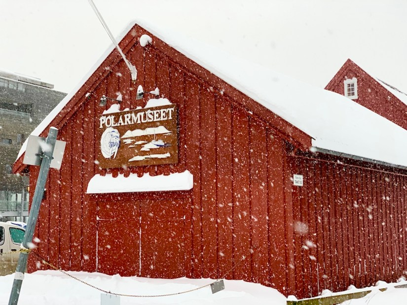Red polar museum building with snow falling in front of it