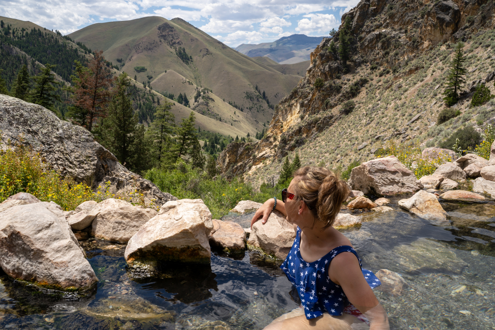 A woman in a blue bathing suit with white stars sitting in a hot spring with a mountain valley landscape behind her.
